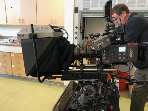 On-camera teleprompter attached to a camera on dolly.